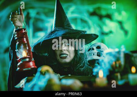 Portrait de sorcière avec terriblement visage et un fanal à la main dans un environnement brumeux creepy envoie le mal. Banque D'Images