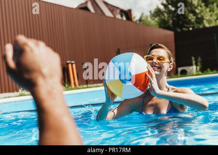 Happy woman jouer avec ballon de plage piscine Banque D'Images