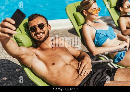 L'homme en prenant le soleil sur les filles avec selfies transats au bord de la piscine Banque D'Images