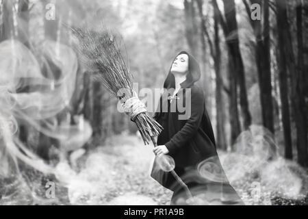 Femme dans un costume de sorcière dans une forêt dense Banque D'Images