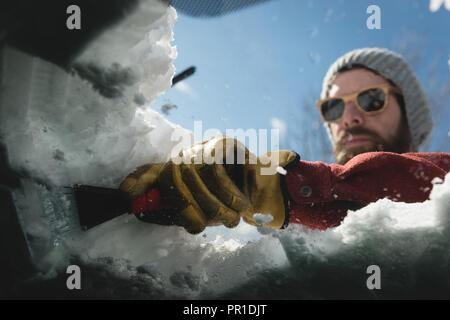 L'homme de neige nettoyage du pare-brise de voiture Banque D'Images