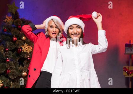 Heureux d'affaires multiculturelles holding santa hats en fonction à nouveau partie de l'entreprise de l'année Banque D'Images