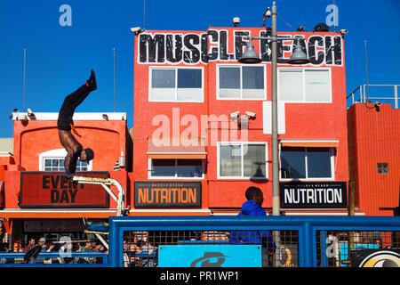 Venice Beach, Los Angeles, Californie - Le 25 février 2018: formation de l'homme devant les yeux et le bâtiment orange muscle beach Banque D'Images