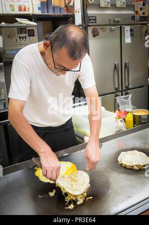 Un chef fait style Hiroshima okonomiyaki à Okonomimura à Hiroshima, au Japon. Banque D'Images