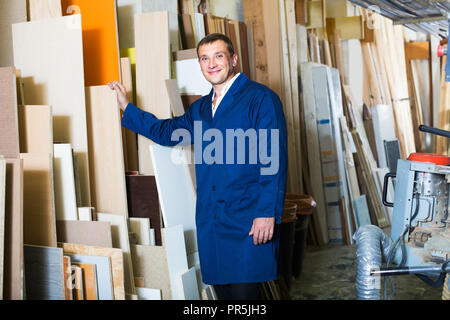 Portrait of smiling man in uniform choisissant gros barre en bois en encadrement atelier Banque D'Images