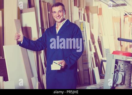 Portrait d'homme en uniforme de l'heureux choix d'une barre en bois en encadrement atelier Banque D'Images