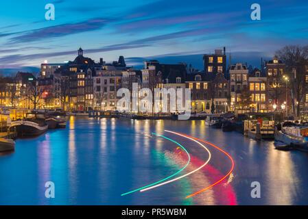 Beau canal à Amsterdam avec la lumière des sentiers passant canal boat. Banque D'Images