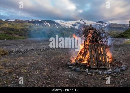 Feu de rituel pendant le solstice d'été en plein milieu de la paysages surréalistes de Thorsmork dans les hautes terres d'Islande. La partie supérieure de l'Eyjafjallajo Banque D'Images