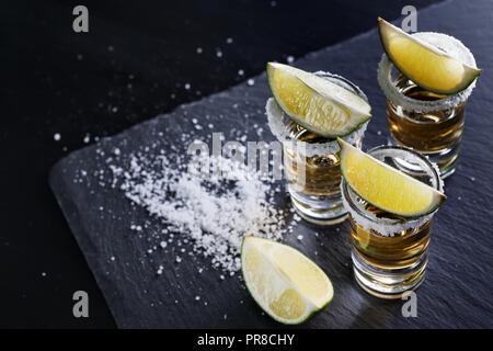 Trois verres de la tequila avec du sel sur la jante et de la chaux sur fond noir. Cocktail sans alcool. Boisson traditionnelle mexicaine Banque D'Images