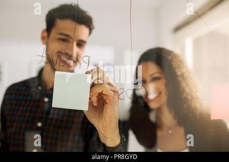 Business couple écrit le post-it collé sur le mur de verre transparent dans le bureau. Collègues de bureau d'affaires de discuter des idées et des plans sur une transpa