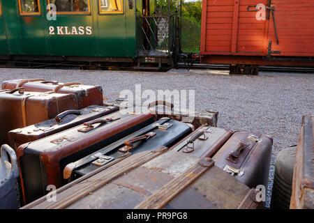 Assurance avec des valises en face d'un vieux train avec un wagon et une deuxième classe verte passanger wagon.