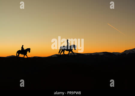 Silhouette of man and woman riding horse sur horizon comme le soleil se couche Banque D'Images