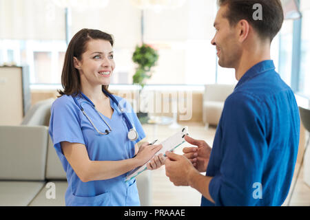 Smiling Nurse Talking to Patient Banque D'Images