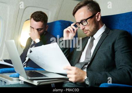 Les gens d'affaires travaillant en avion Banque D'Images