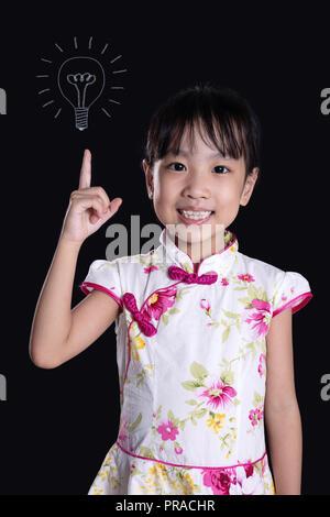 Chinois asiatique petite fille montre de l'index jusqu'à l'ampoule en fond noir isolé Banque D'Images