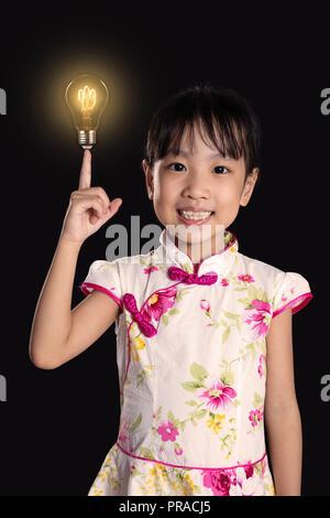 Chinois asiatique petite fille montre de l'index jusqu'à l'ampoule dans l'arrière-plan noir isolé Banque D'Images