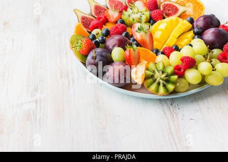 Les fruits sains et les baies, Fraises Framboises plaque Oranges Pommes Prunes Raisins kiwis mangues les bleuets, sur le tableau blanc woorden Banque D'Images
