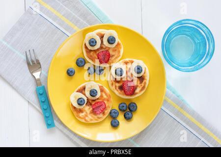 Petit-déjeuner de crêpes pour les enfants. Crêpes en forme animal mignon drôle sur une plaque jaune. Vue d'en haut. L'art de l'alimentation Banque D'Images