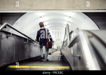 Vue arrière du hipster businessman walking dans les escaliers dans le métro, se rendre à leur lieu de travail.