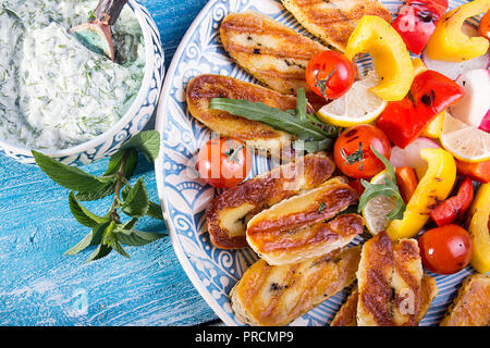 Ensemble prédéfini de fromage et des collations. Halloumi grillé, poivre, zuccini, tomates cerise, radis et de sauce tzatziki sur sur bleu fond de bois. Plus de