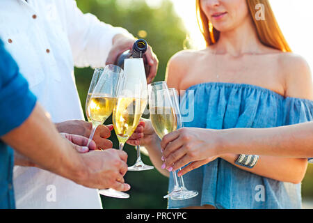 Happy friends pouring champagne vin mousseux dans des verres en plein air sur une plage. Sunset beach party Banque D'Images