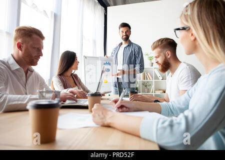 L'atteinte de meilleurs résultats ensemble. Jeune homme moderne effectuant une présentation d'affaires tout en se tenant dans la salle du conseil. Banque D'Images