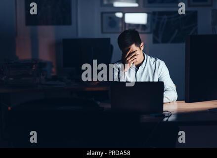 Épuisé Asian businessman travaillant tard dans la nuit dans un bureau Banque D'Images