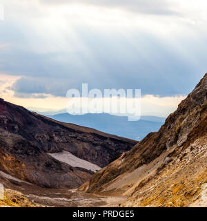 Les rayons du soleil font leur chemin à travers les nuages. Coucher du soleil sur le volcan Mutnovsky, péninsule du Kamchatka, Russie Banque D'Images
