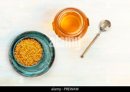 Une saine alimentation biologique. Une photo prise à la verticale du pollen, un pot de miel, et d'un coup de cuillère, vintage au-dessus sur un fond clair avec copie espace Banque D'Images