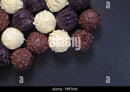 De délicieuses truffes au chocolat noir sur fond de pierre. Assortiment de chocolats noir et au lait blanc dans le chocolat. Banque D'Images
