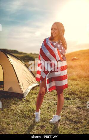 Happy young woman bénéficie d'une journée ensoleillée dans la nature. Elle est enveloppée de drapeau américain devant une tente de camping. Banque D'Images