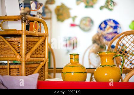 Des pots en argile décoratifs, des bols et des vases debout sur étagère dans la cuisine. Peintures abstraites et des dessins colorés sur le mur en arrière-plan. Sunligh lumineux