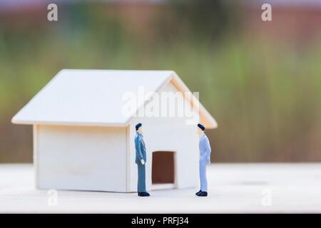 Accueil négocier, immobilier, maison, prêt prêteur hypothécaire inversé concept: deux hommes d'affaire/petite résidence sur table en bois et b
