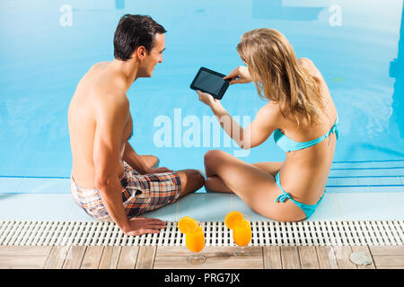 Couple heureux à la piscine using digital tablet Banque D'Images