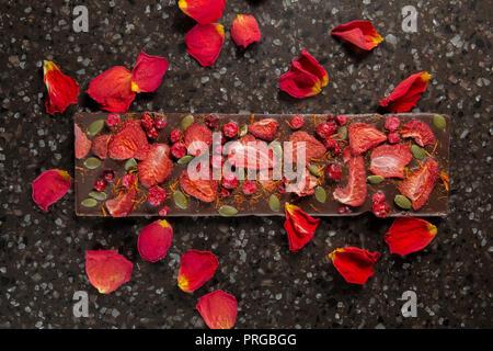 Chocolat artisanal bar avec les fraises et les canneberges séchées dans des pétales de rose. Banque D'Images