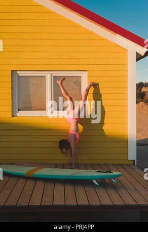 Young woman in pink bikini debout sur les mains contre bâtiment jaune avec voile à proximité au Portugal Banque D'Images