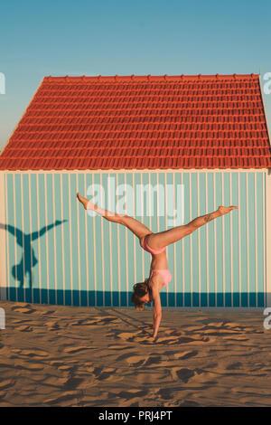 Young woman in pink bikini debout sur les mains contre le bâtiment au Portugal Banque D'Images