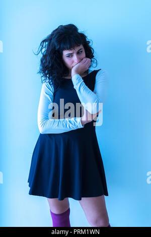 Portrait d'une belle jeune femme concernée dans une élégante robe debout devant un mur blanc.