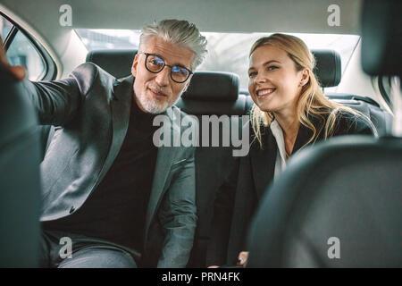 Senior businessman et son assistante assise dans la banquette arrière de la voiture et à la route en souriant. Les gens d'affaires voyageant en cabine. Banque D'Images