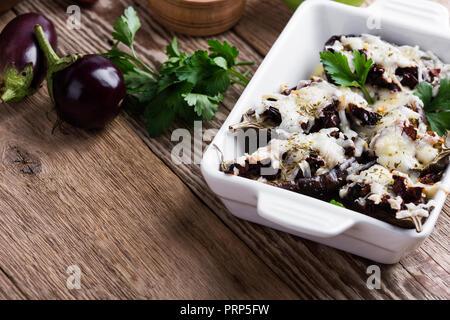 Aubergines farcies aux tomates séchées et de mozzarella en plat de céramique sur table en bois rustique Banque D'Images