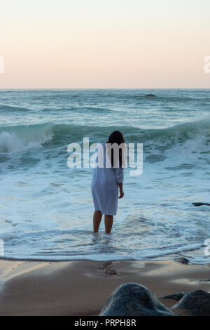 Femme sur une belle plage vide pendant le lever du soleil, comtemplating l'océan. Banque D'Images