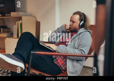 L'homme à l'emploi temporaire de vous détendre sur une chaise longue en regardant son ordinateur portable et la pensée. Programmeur travaillant sur un nouveau développement de logiciels. Banque D'Images