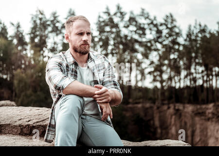 Homme barbu sentiment réfléchi après des problèmes personnels alors qu'il était assis sur son propre
