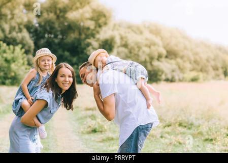 Heureux parents usurpation de fils et fille de l'été sur les chapeaux de paille feild Banque D'Images