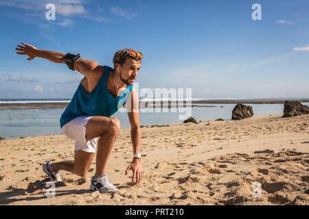 L'homme athlétique de brassard faisant se jette au cours de l'entraînement sur mer Banque D'Images