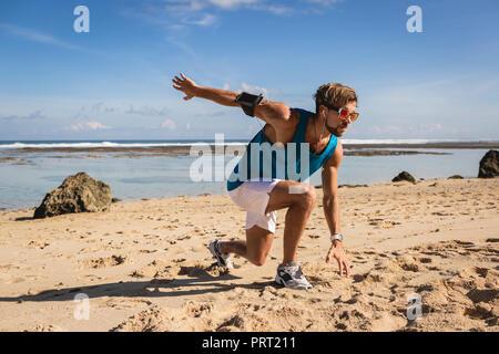 Bel homme athlétique faisant se jette au cours de l'entraînement sur mer Banque D'Images