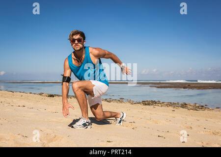 Athletic man doing se jette au cours de l'entraînement sur la mer près de la plage Banque D'Images