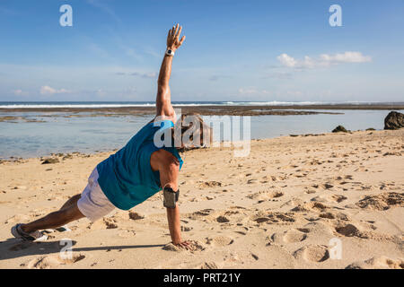 L'homme sportif faisant planche latérale sur la plage de sable Banque D'Images