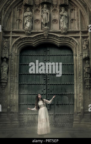 Femme en blanc en face de la grande porte de l'hôtel particulier. Banque D'Images