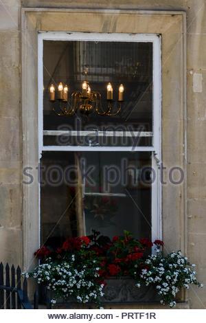 Close up de droit à la recherche dans une fenêtre d'un chandelier allumé à l'intérieur et une boîte sous la fenêtre, baignoire, Somerset, England, UK Banque D'Images